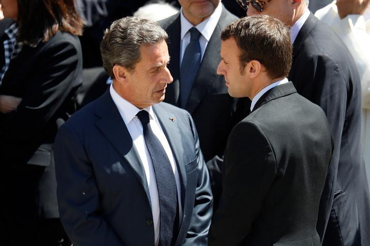 Nicolas Sarkozy (L), head of France's Les Republicains political party and former French president speaks with French Economy Minister Emmanuel Macron (R) as they attend an official funeral ceremony for late former French Socialist Prime Minister Michel Rocard at the Hotel des Invalides in Paris, France, July 7, 2016. REUTERS/Charles Platiau/File Photo