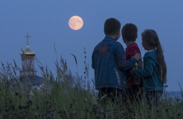 REPRESENTATIVE IMAGE: Children look at the moon as they gather in the settlement of Poschupovo in Ryazan region, Russia, September 27, 2015. REUTERS/Maxim Shemetov/Files