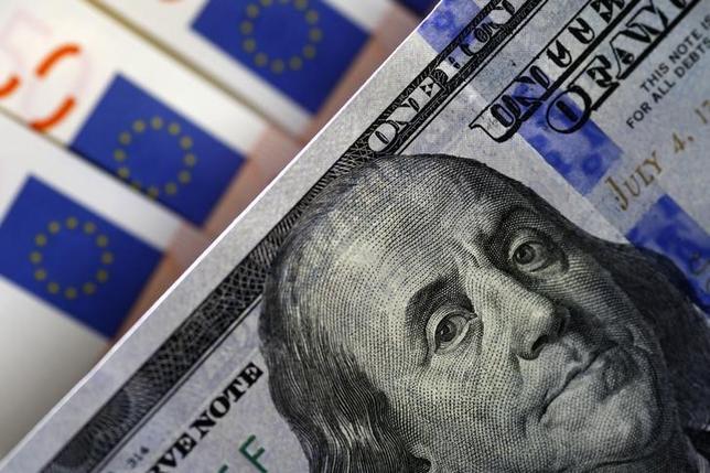 4月26日、終盤のニューヨーク外為市場では、ドルが主要通貨に対し一時つけた高値から上げ幅を縮小した。写真はドルとユーロの紙幣、2015年3月撮影(2017年 ロイター/Stoyan Nenov)