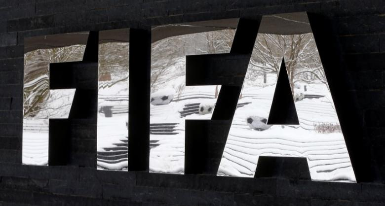 The snow-covered landscape is reflected in a logo in front of FIFA headquarters in Zurich, Switzerland, January 10, 2017.   REUTERS/Arnd Wiegman