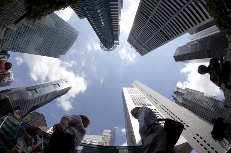 People walk past office buildings at the central business district in Singapore April 14, 2015. REUTERS/Edgar Su/Files