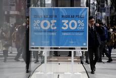 Un hombre usa su celular mientras camina cerca de un aviso de descuento en una tienda en Tokio, Japón. 25 de febrero 2016.  Los precios subyacentes al consumidor de Japón crecieron en marzo a un ritmo más lento que lo previsto y el gasto de los hogares cayó más que lo esperado, en una señal preocupante para el banco central de ese país. REUTERS/Yuya Shino