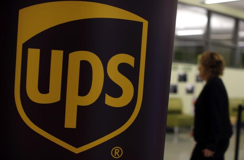 FILE PHOTO: A woman walks past a sign bearing the logo of United Parcel Service (UPS) at a job fair in Chicago, Illinois, October 18, 2014.  REUTERS/Jim Young