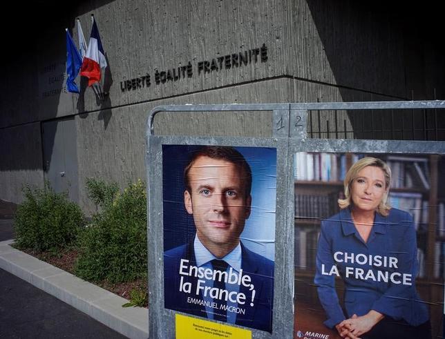4月30日、5月7日に行われるフランス大統領選決選投票で、どちらの候補が勝っても、争点の慢性的な失業や治安問題を解決できない──。多くの有権者がこうした見方をしていることが、最新の世論調査結果で分かった。写真のマクロン氏、ルペン氏両候補者のポスターはリオンで撮影(2017年 ロイター/Robert Pratta)
