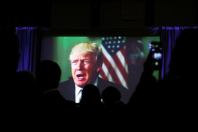 Guests watch a video of U.S. President Donald Trump as he addresses the 15th Plenary Assembly of the World Jewish Congress in New York City, U.S., April 23, 2017. REUTERS/Brendan McDermid/Files