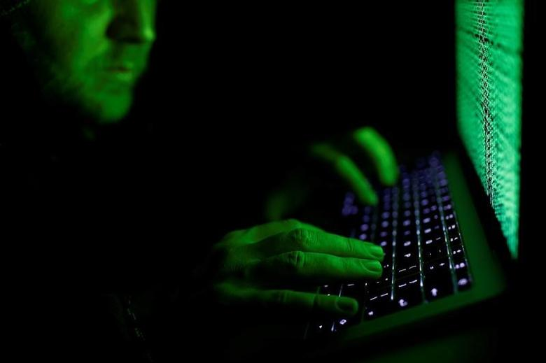 A man types on a computer keyboard in front of the displayed cyber code in this illustration picture taken on March 1,  2017. REUTERS/Kacper Pempel/Illustration