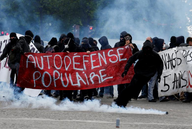 Tear gas floats in the air as demonstrators walk behind a banner which reads, ''Populist Self-Defence'' during clashes at the traditional May Day labour union march in Paris, France, May 1, 2017.   REUTERS/Gonzalo Fuentes
