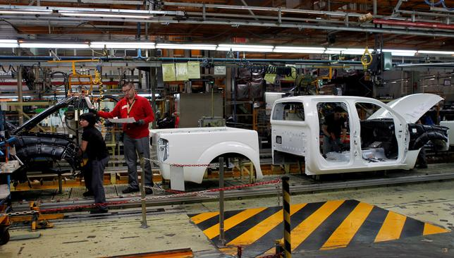 FILE PHOTO: Nissan Motor staff work in a manufacturing chain at the Zona Franca Nissan factory near Barcelona May 23, 2012. REUTERS/Albert Gea/File Photo