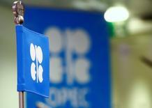 Una bandera de la OPEP es vista adelante del logo en Viena, Austria. 24 de octubre 2016.   La producción petrolera de la OPEP bajó por cuarto mes seguido en abril, dado que Arabia Saudita mantuvo su bombeo por debajo de su objetivo y porque las actividades de mantenimiento y conflictos disminuyeron la actividad en Nigeria y Libia, que están exentas de los recortes. REUTERS/Leonhard Foeger