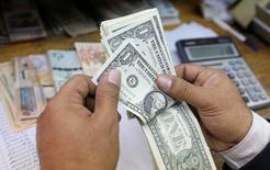 Imagen de archivvo de una persona contando dólares en una casa de cambios en El Cairo, mar 7, 2017. El dólar tocó un máximo de seis semanas el martes frente al yen, impulsado por un aumento de los rendimientos de los bonos del Tesoro de Estados Unidos después de que el Secretario del Tesoro, Steven Mnuchin, se refirió a la posibilidad de una emisión de notas con vencimiento ultralargo.  REUTERS/Mohamed Abd El Ghany