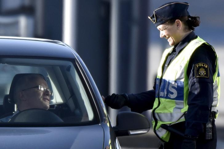 A police officer checks the identification of a driver at Lernacken, on the Swedish side of the Oresund strait, November 12, 2015. REUTERS/Nils Meilvang/Scanpix