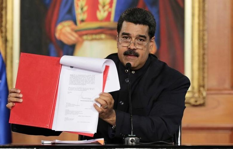 Venezuela's President Nicolas Maduro holds a document as he speaks during a ceremony at Miraflores Palace in Caracas, Venezuela May 1, 2017. Miraflores Palace/Handout via REUTERS