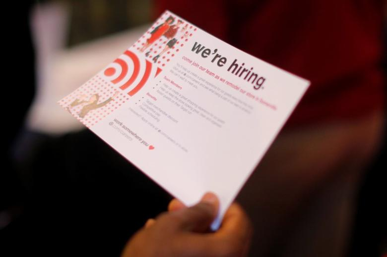 A job seeker holds a ''We're Hiring'' card while talking to a representative from Target at a City of Boston Neighborhood Career Fair on May Day in Boston, Massachusetts, U.S., May 1, 2017.   REUTERS/Brian Snyder
