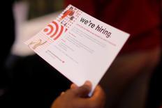 """Un solicitante de empleo tiene una tarjeta que dice """"Estamos contratando"""" mientras habla con un representante de Target en una feria del trabajo en Boston, Estados Unidos. 1 de mayo 2017.   Los empleadores privados en Estados Unidos sumaron 177.000 puestos de trabajo en abril, levemente más de lo esperado por economistas, según un informe de un procesador de nóminas divulgado el miércoles.REUTERS/Brian Snyder"""