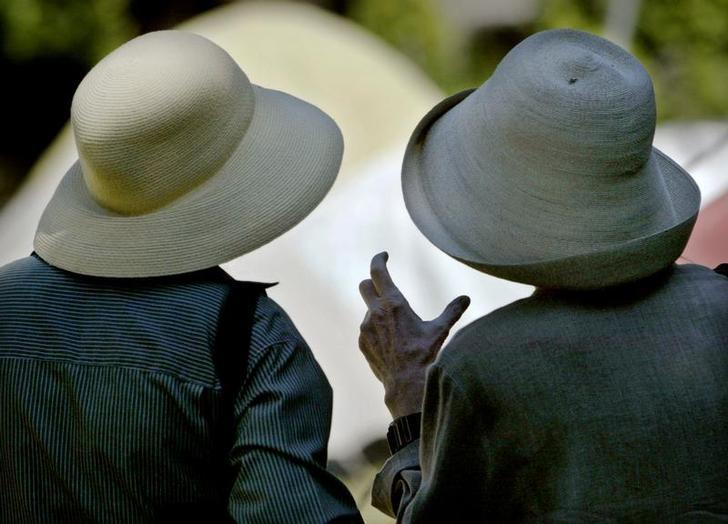 Wearing sunhats elderly ladies chat in Victory Square in dowtown VancouverJuly 22, 2003.  REUTERS/Andy Clark