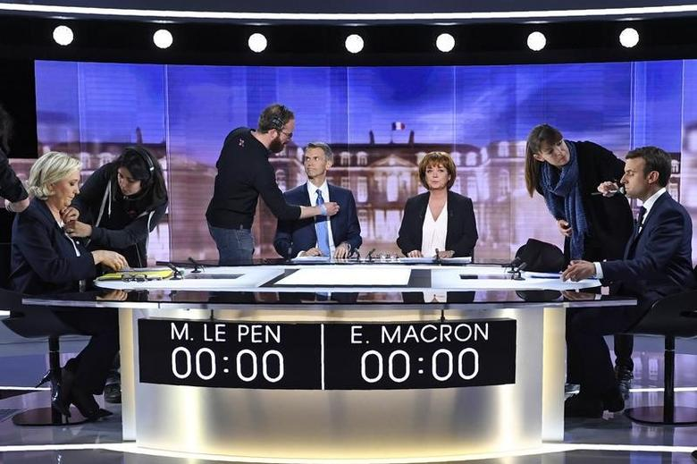 (From L) French presidential election candidate for the far-right Front National (FN) party, Marine Le Pen, French journalist Christophe Jakubyszyn, French journalist Nathalie Saint-Cricq and French presidential election candidate for the En Marche ! movement, Emmanuel Macron are prepared prior to the start of a live brodcast face-to-face televised debate in television studios of French public national television channel France 2, and French private channel TF1 in La Plaine-Saint-Denis, near Paris, France, May 3, 2017.   REUTERS/Eric Feferberg/Pool