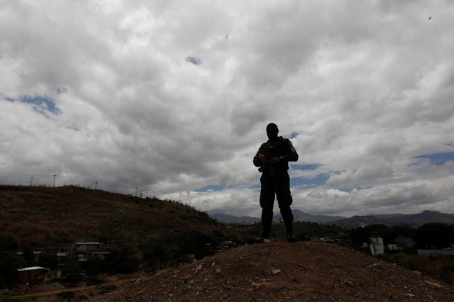 A member of the military police keeps watch during a routine foot patrol at El Pedregal neighbourhood Tegucigalpa, Honduras, May 3, 2017. REUTERS/Jorge Cabrera