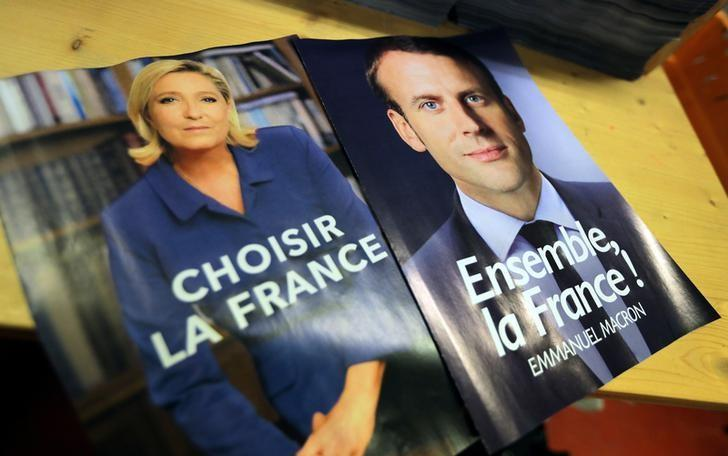 Electoral documents for the upcoming second round of 2017 French presidential election are displayed as registered voters will receive an envelope containing the declarations of faith of each candidate, Emmanuel Macron (R) and Marine Le Pen (L), along with the two ballot papers for the May 7 second round of the French presidential election, in Nice, France, May 3, 2017. REUTERS/Eric Gaillard