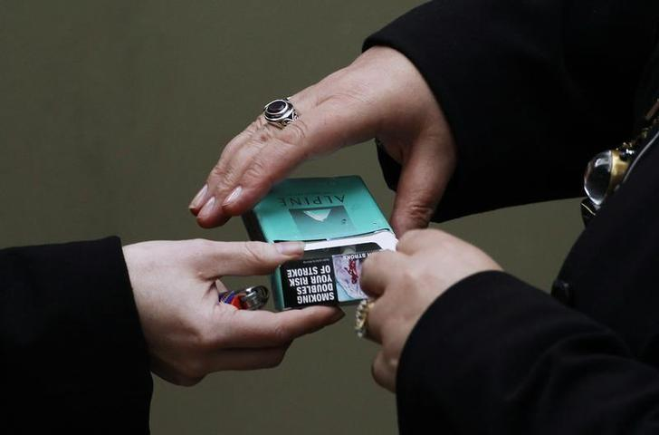 Women handle a cigarette pack in central Sydney October 12, 2011. REUTERS/Daniel Munoz/Files