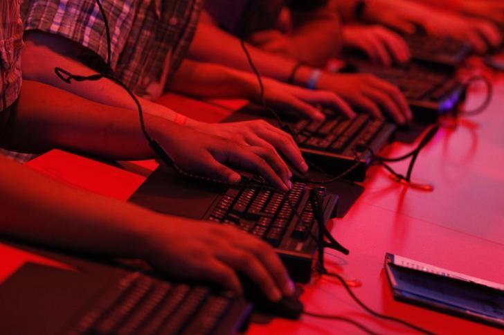 FILE PHOTO - Visitors play use keyboards as they play during the Gamescom 2012 fair in Cologne August 16, 2012. REUTERS/Ina Fassbender