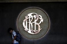 Un hombre camina cerca del logo del Banco Central de Reserva de Perú en un edificio en Lima, Abril 7, 2015. Analistas redujeron sus proyecciones de crecimiento económico de Perú para este año y elevaron sus expectativas de inflación por encima del techo del rango meta oficial, dijo un sondeo del Banco Central publicado el jueves. REUTERS/Mariana Bazo
