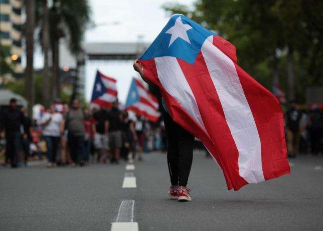 FILE PHOTO: A person carries a Puerto Rican national flag during a protest against the government's austerity measures as Puerto Rico faces a deadline on Monday to restructure its $70 billion debt load or open itself up to lawsuits from creditors, in San Juan, Puerto Rico May 1, 2017. REUTERS/Alvin Baez