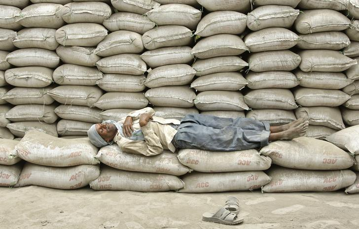 A labourer takes a nap on the stacked cement sacks of ACC company on the outskirts of the northern Indian city of Allahabad June 22, 2012. REUTERS/Jitendra Prakash/files