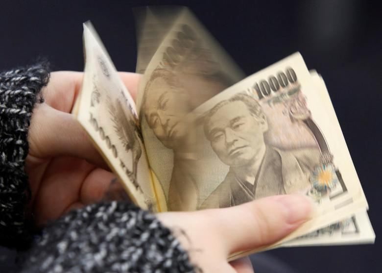 FILE PHOTO: A woman counts Japanese 10,000 yen notes in Tokyo, in this February 28, 2013 picture illustration.   REUTERS/Shohei Miyano/File Photo