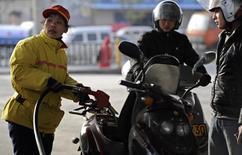 Un empleado llena el tanque de una motocicleta mientras otro espera para comprar combustible en una estación de servicio en Hefei, provincia de Anhui, China, el 23 de marzo de 2012. El desplome en los mercados del petróleo esta semana a un mínimo de seis meses probablemente se debió a preocupaciones sobre el crecimiento económico chino, a los inventarios persistentemente altos y a el posicionamiento de fondos. REUTERS/Stringer