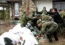 جنود كنديون يضعون أكياسا من الرمل أمام منزل في مقاطعة سكنية في كيبيك يوم الأحد . تصوير: كريستين موشي - رويترز