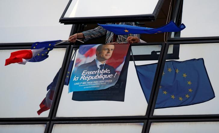 A supporter holds a campaign poster of Emmanuel Macron and European Union flags after results were announced in the second round of 2017 French presidential election at the campaign headquarters in Paris, France, May 7, 2017. REUTERS/Gonzalo Fuentes
