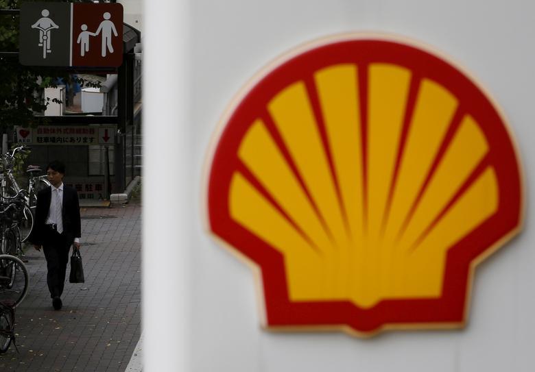 FILE PHOTO: A man walks behind a signboard of Showa Shell Sekiyu at its gas station in Tokyo, Japan, November 11, 2015. REUTERS/Yuya Shino/File Photo