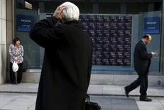 Un hombre mira un tablero electrónico que muestra información de la bolsa de Japón fuera de una correduría en Tokio, Japón. 2 de marzo 2016. Las bolsas de Asia caían el martes luego de un cierre estable en Wall Street, en momentos en que los inversores buscaban el siguiente catalizador tras las elecciones presidenciales de Francia, y el petróleo subía por las expectativas de que unos recortes a la producción de la OPEP se extenderán. REUTERS/Thomas Peter - RTS8VY3