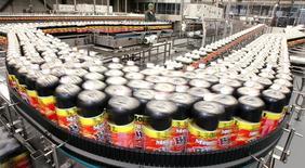 Un trabajador vigila la calidad de las botellas de la soda Big Cola en una planta en Huejotzingo en México. 11 de noviembre de 2005. El grupo peruano de bebidas AJE dejará de operar directamente en Brasil, México, Venezuela y otros dos países del sudeste asiático y venderá a través de franquicias, lo que ayudará a mejorar su perfil crediticio, dijo el martes la compañía. REUTERS/Daniel Aguilar