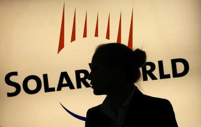 A woman is silhouetted against the logo of Germany's SolarWorld at the reception desk of the company's  extraordinary shareholders meeting in Bonn August 7, 2013.  REUTERS/Wolfgang Rattay