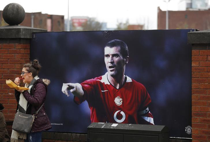 Britain Soccer Football - Manchester United v West Bromwich Albion - Premier League - Old Trafford - 1/4/17 General view as a fan stands alongside a picture of Roy Keane outside the stadium before the match Action Images via Reuters / Lee Smith Livepic /Files