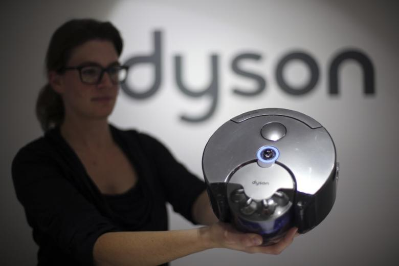 A Dyson employee shows a Dyson 360 Eye robot vacuum cleaner during the IFA Electronics show in Berlin September 4, 2014. REUTERS/Hannibal Hanschke