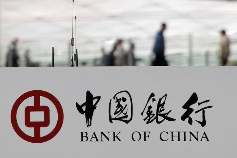 Pedestrians are seen behind the logo of Bank of China on its ATM machine in Beijing, China, in this March 28, 2016 file photo. REUTERS/Kim Kyung-Hoon/File photo
