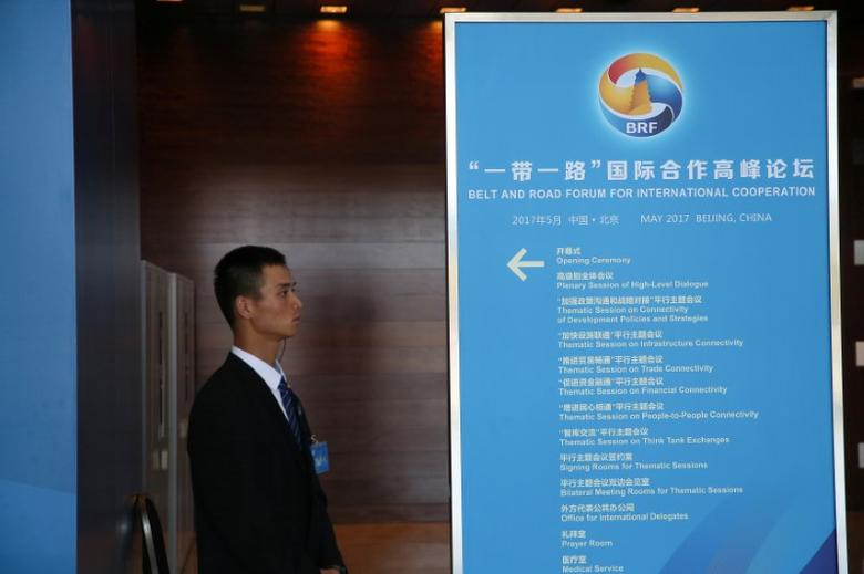 A staff member stands next to a sign for the Belt and Road Forum at the National Convention Centre in Beijing, China May 13, 2017.  REUTERS/Stringer