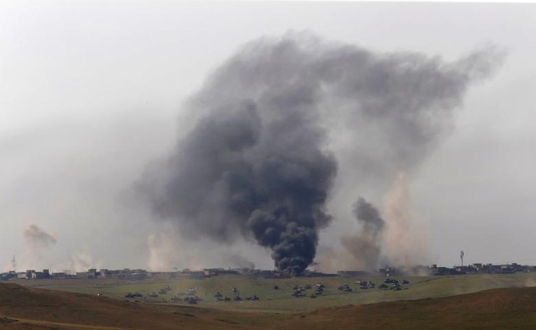 Smoke is seen as members of the Iraqi Army clash with Islamic State fighters at a frontline in north west of Mosul. REUTERS/Danish Siddiqui