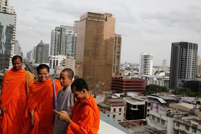 5月15日、タイ国家経済社会開発庁(NESDB)が発表した第1・四半期の国内総生産(GDP)は、季節調整済みで前期比1.3%増となり、4年ぶり高水準となった。写真は僧侶たち。バンコクのショッピングモールで昨年8月撮影(2017年 ロイター/Jorge Silva)