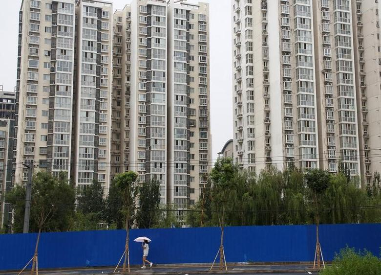 A woman walks past residential buildings in Beijing, July 15, 2016. Picture taken July 15, 2016. REUTERS/Thomas Peter