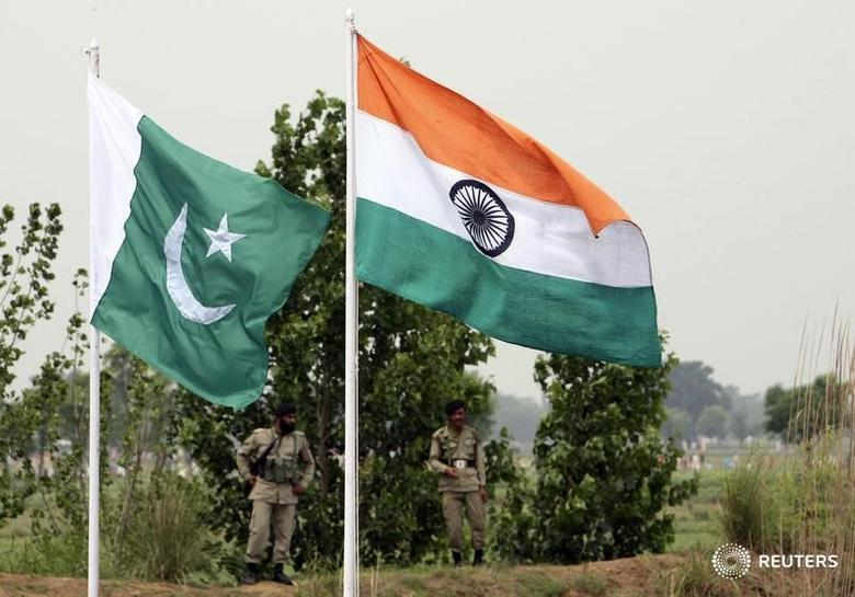 FILE PHOTO: Pakistani rangers stand near the Indian (R) and Pakistani national flags during an annual fair near Pakistan border in Chamliyal, 45 km (28 miles) west of Jammu, June 26, 2008. REUTERS/Amit Gupta/Files