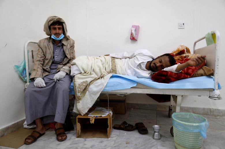 A man sits next to a relative infected with cholera at a hospital in Sanaa. REUTERS/Khaled Abdullah