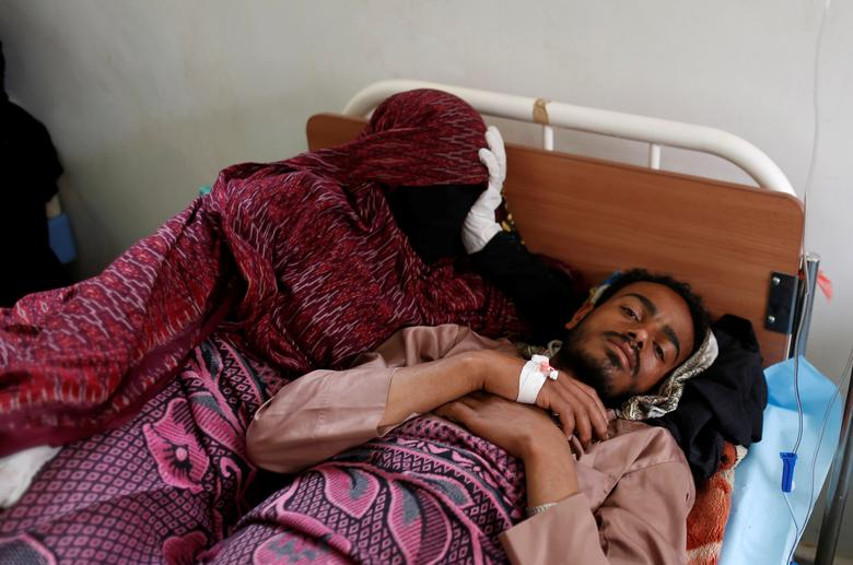 A woman lies next to her husband who is infected with cholera at a hospital in Sanaa. REUTERS/Khaled Abdullah