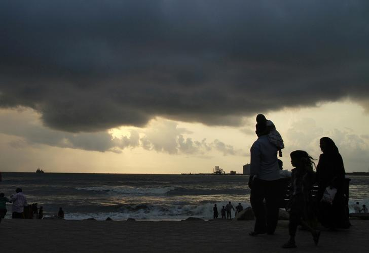 Beachgoers stroll along the Fort Kochi beach as clouds hover over the Arabian Sea in Kerala May 23, 2013. REUTERS/Sivaram V/Files