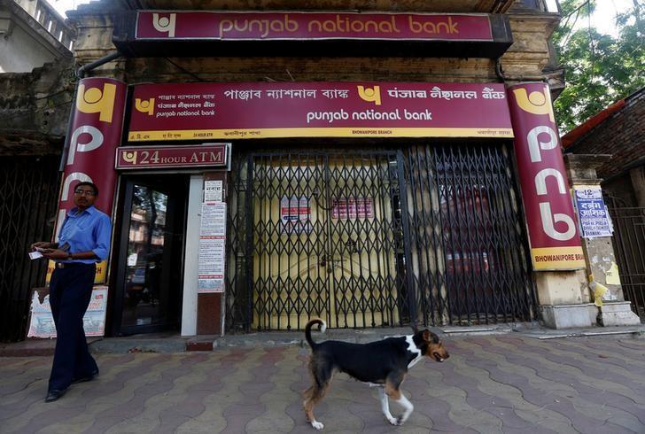 A man exits Punjab National Bank's building as a stray dog walks past in Kolkata, India May 16, 2017. REUTERS/Rupak De Chowdhuri