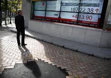 Un hombre mira un tablero electrónico que muestra el promedio Nikkei de Japón fuera de una correduría en Tokio, 1 de diciembre 2016.El índice Nikkei de la bolsa de Tokio avanzó el martes gracias a una caída del yen y un repunte de las acciones estadounidenses a máximos históricos. REUTERS/Kim Kyung-Hoon