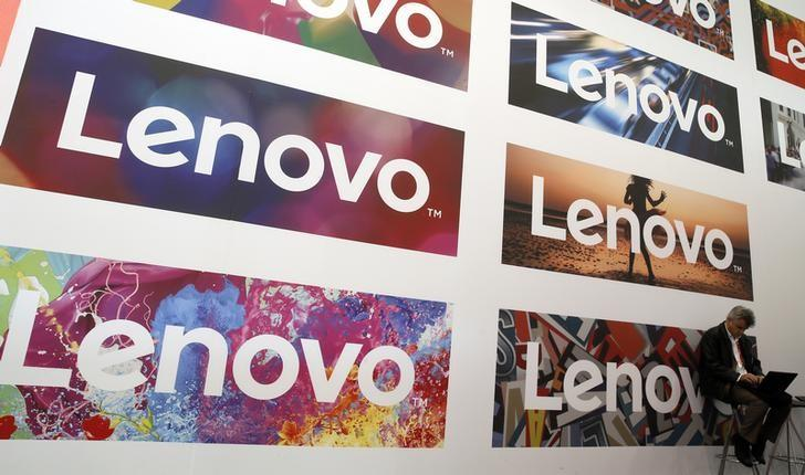 FILE PHOTO: A man uses his laptop next to Lenovo's logos during the Mobile World Congress in Barcelona, Spain February 25, 2016. REUTERS/Albert Gea