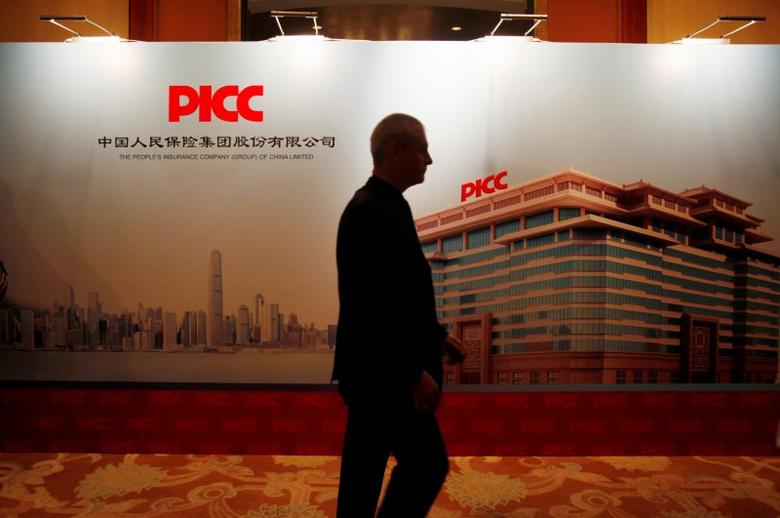 A man walks past a backdrop during an investors meeting of The People's Insurance Company (Group) of China Ltd (PICC) in Hong Kong November 22, 2012.  REUTERS/Bobby Yip/File Photo